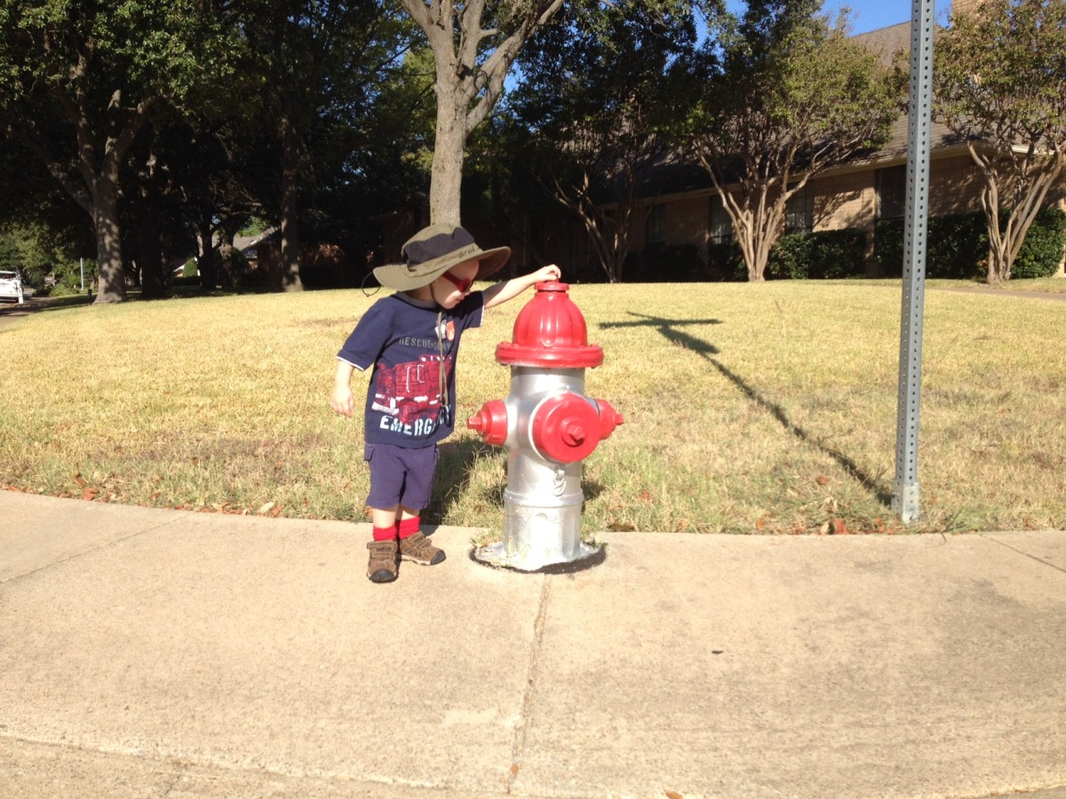 Liam wearing a fire truck shirt and standing next to a fire hydrant